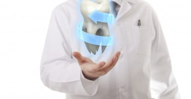 Male doctor showing a molar tooth